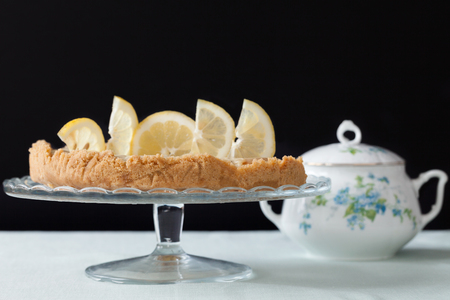 stand teapot: Cake stand with lemons tart and porcelain teapot in the background. Stock Photo