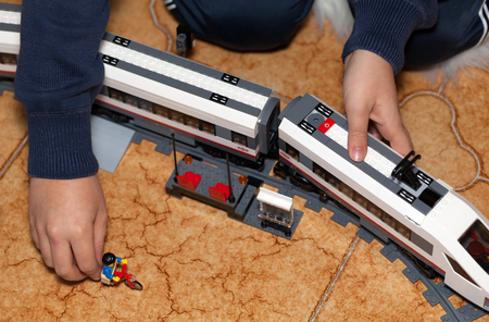 highspeed: ROME, ITALY - DECEMBER 28, 2015: Child playing with the high-speed passenger train from LEGO CITY . Lego is a popular line of construction toys manufactured by the Lego Group.
