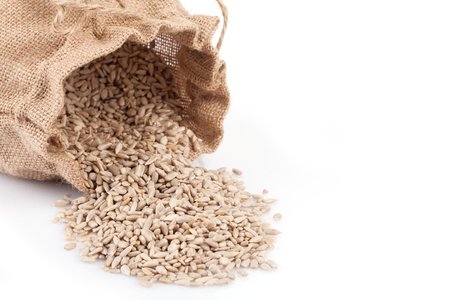 shelled: Closeup of sack with shelled sunflower seeds on white background. Stock Photo