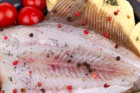 vegetable tin: Detail of raw skinned turbot fish on potato slices, seasoned with red and black pepper grains, black salt, thyme and cherry tomatoes.