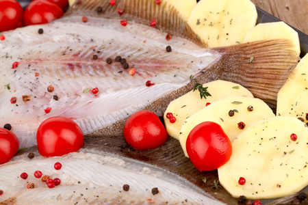 red skinned: Closeup of skinned raw turbot fish with potato slices, seasoned with cherry tomatoes, thyme, red and black pepper grains and black salt, ready to be cooked in the oven.