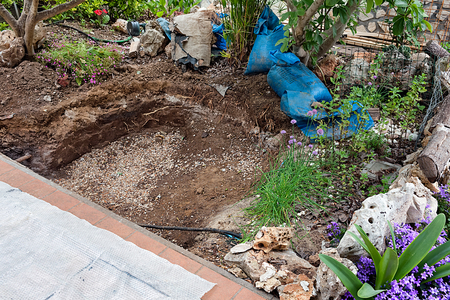 Hole excavated in the garden for artificial pond construction.