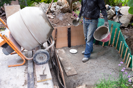 vivarium: Mason waiting for the fresh cement to be prepared by the cement mixer, during the building of artificial pond in the garden. Stock Photo