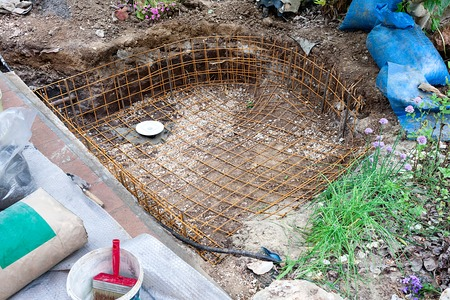 vivarium: Preliminary step in an artificial pond construction: fixing the iron network for the cement reinforcement. Stock Photo