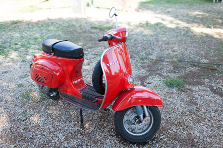 manufactured: SANTA MARINELLA, LAZIO, ITALY - SEPTEMBER 28, 2014: Red vintage 50s Vespa Scooter, iconic symbol of Italy, manufactured by Piaggio. The Vespa has evolved from a single model motor scooter manufactured in 1946 by Piaggio & Co. S.p.A. of Pontedera, Italy-to