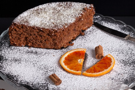 icing sugar: Homemade soft cake made with dark chocolate, orange and hazelnuts and decorated with icing sugar, orange slices and cinnamon rolls. Stock Photo