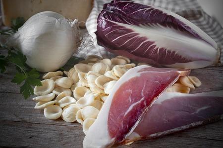 cebolla blanca: Ingredients used to prepare a typical italian pasta recipe: orecchiette, speck, red chicory, white onion and parsley. Foto de archivo