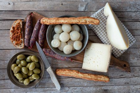 caciocavallo: Overhead shot of assorted italian cheese (caciocavallo and Bastardo cheese), smoked sausages, cipolle borettane ( a variety of pickled onions), green olives and bruschetta with chili peppers sauce.