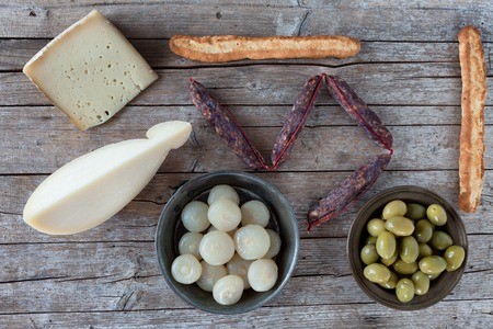 caciocavallo: Overhead shot of assorted italian cheese (caciocavallo and Bastardo cheese), smoked sausages, cipolle borettane ( a variety of pickled onions), green olives and homemade bread sticks.