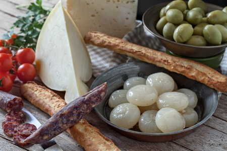 caciocavallo: Assorted italian cheese (caciocavallo and Bastardo cheese), smoked sausages, cipolle borettane ( a variety of pickled onions), green olives, cherry tomatoes and bread sticks. Stock Photo