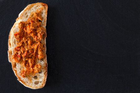 overhead shot: Overhead shot of slice of bread with hot chili pepper sauce, over black background.