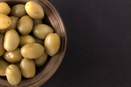brine: Bowl with italian green olives from Apulia, pickled in brine. Overhead shot on black background. Stock Photo