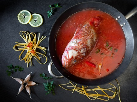 scorpionfish: Preparing red scorpionfish sauce for the fettucine pasta, typical Italian recipe. Overhead shot of table with ingredients and pan with the fish and tomato sauce. Stock Photo