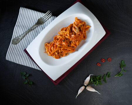 scorpionfish: Overhead shot of plate with fettuccine pasta garnished with tomato and red scorpionfish sauce, prepared by a traditional italian recipe.