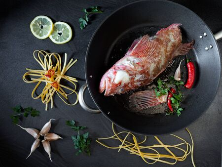 scorpionfish: The first step of preparing fettuccine pasta with scorpionfish: fry the fish in a pan with olive oil, parsley,garlic and chili pepper.