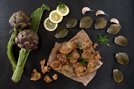 Draufsicht der Tabelle mit gebratenen Artischocken auf dem Küchenpapier, verziert mit Scheiben der Zitrone, der tadellosen Blätter und des Knoblauchs. Standard-Bild