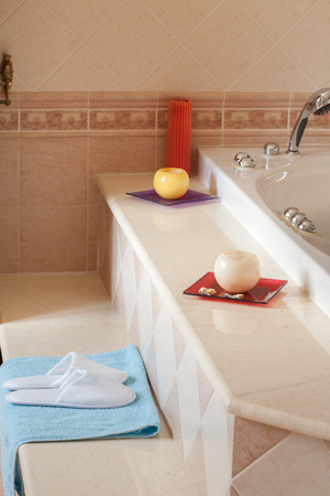comfy: Comfy spa-style slippers on blue towel besides the jacuzzi bathtub in home bathroom.