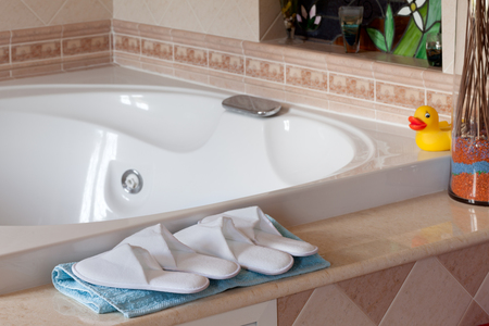 comfy: Comfy spa-style slippers near jacuzzi bathtub in home bathroom. Stock Photo