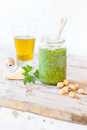 extra virgin olive oil: Jar with parsley pesto and ingredients to prepare it: parsley, parmesan cheese, extra virgin olive oil, hazelnuts and white pepper. Stock Photo