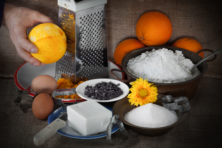 chocolate chips cookies: Ingredients necessary for the preparation of orange chocolate chips cookies: oranges, eggs, butter, flour, sugar and chocolate chips and cooks hand grating orange on grater.