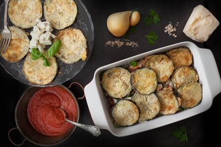 scamorza: Preparing eggplant parmigiana, sixth step, fried eggplant slices above cheese and tomato sauce layer. Stock Photo