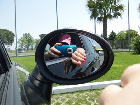 rearview: Woman taking selfie in the rearview mirror of the car.