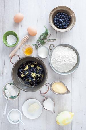 baking powder: Pancake recipe with yogurt, ingredients: blueberries, flour, cornmeal, lemon, honey, thyme, butter, eggs, sugar, milk, yogurt, baking powder. Flat lay.