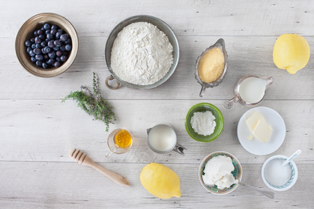 baking powder: Ingredients for cooking lemon blueberry pancakes: blueberries, flour, cornmeal, lemon, honey, thyme, butter, sugar, milk, buttermilk, baking powder. Flat lay.