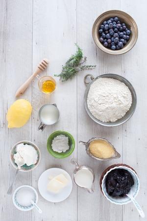baking powder: Ingredients necessary to prepare the whole wheat blueberry pancakes: blueberries, flour, cornmeal, lemon, honey, thyme, butter, blueberries jam, sugar, milk, buttermilk, baking powder. Flat lay. Stock Photo