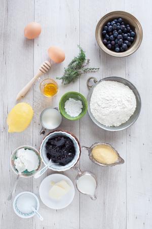 baking powder: Homemade blueberry pancakes ingredients: blueberries, flour, cornmeal, lemon, honey, thyme, butter, eggs, blueberries jam, sugar, milk, buttermilk, baking powder. Flat lay. Stock Photo