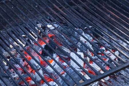 briquettes: Empty barbecue grill with burning charcoal briquettes under. Stock Photo