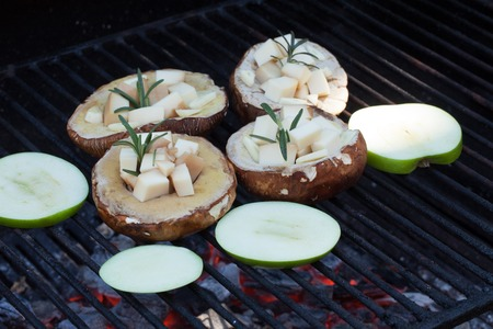 Cooking porcini mushrooms filled with scamorza cheese and green apples on hot barbecue grill.