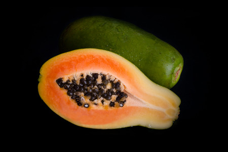 sectioned: Papaya fruit, whole and sectioned, isolated on black background.