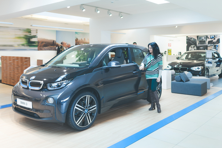 i3: ROME, ITALY - MARCH 10, 2014: Woman looking at the new five-door urban electric car BMW I3 at dealer showroom.The i3 is BMW s first zero emissions mass-produced vehicle due to its electric powertrain.