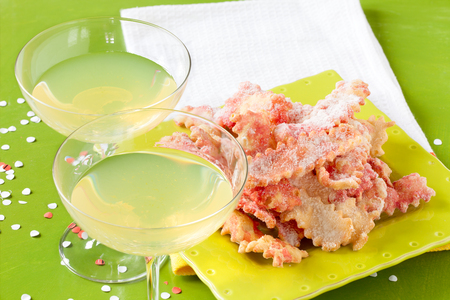 chiacchiere: Lemon cocktail and fritters, typical Italian  food and drink in the carnival period. Stock Photo