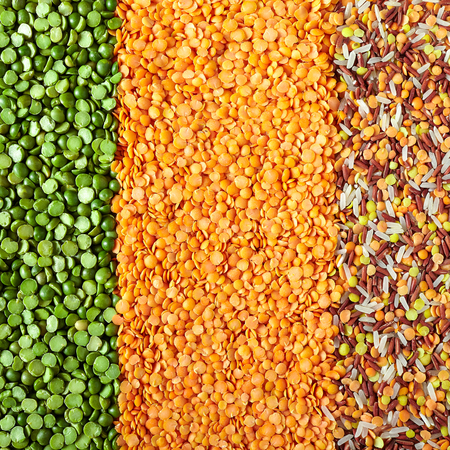 Vertical layers of dried legumes, from left to right: green split peas, red lentils and mix of red Thai rice, white perfume rice, red and yellow decorticated lentils.