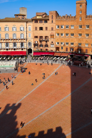 SIENA, ITALY - March 14, 2014: The shadow of Torre del Mangia in Piazza del Campo the principal public space of the historic center of Siena.