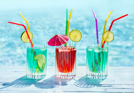 Glasses with mint and cherry juice on the side of a swimming pool with blue water in the background. Stock Photo
