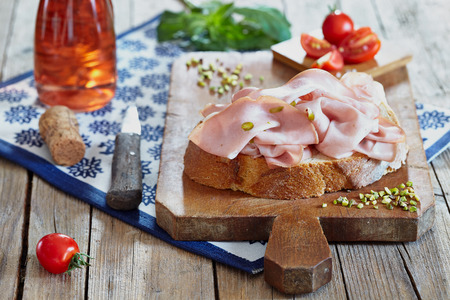 Mortadella with pistachio nuts on bread slice, with cherry tomatoes and rose sparkling wine. Stock Photo - 85261339
