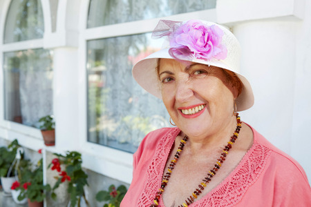 Portrait of a cheerful senior woman dressed retro style with beads and hat, looking at the camera. Stock Photo