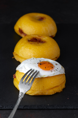 Bulz, a traditional Romanian meal composed of polenta balls stuffed with sheep cheese and roasted smoked sausage, and served with a  soft fried egg. Stock Photo