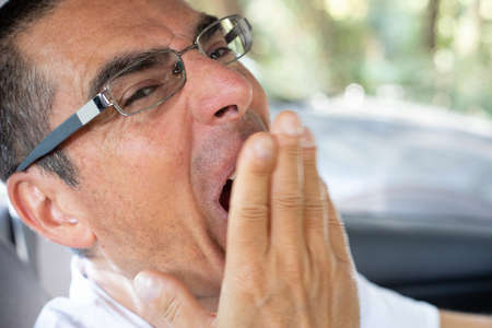 Man tired yawning with his hand in front of the mouth