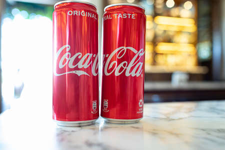 ASSISI, ITALY - AUGUST 22, 2020: Cold Coca-Cola cans on a table in a bar. Coca-Cola, or Coke, is a carbonated soft drink manufactured by The Coca-Cola Company.