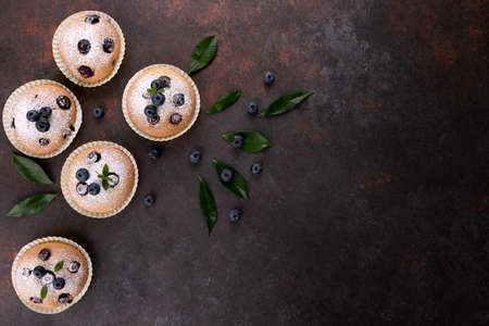 Blueberry muffins on brown wood background flat lay with copy space Stok Fotoğraf