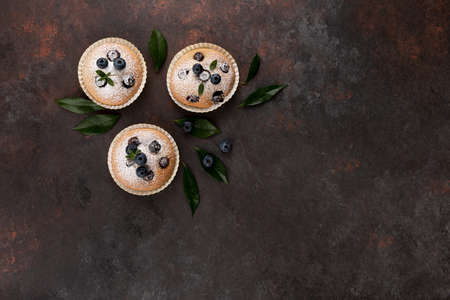 Blueberry muffins top view brown flat lay wooden background with copy space