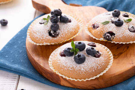 Closeup of blueberry muffins on wooden board and blue kitchen napkin