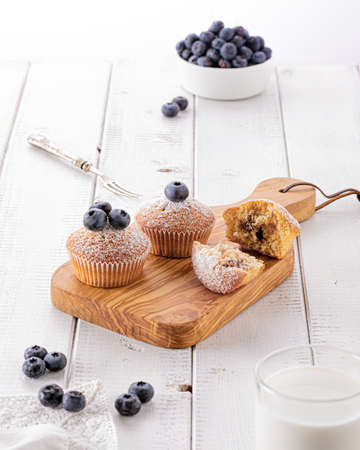 Fresh baked blueberry muffins on wooden board on a white wooden table in the morning light