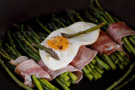 Bacon wrapped asparagus with a fried egg on the top