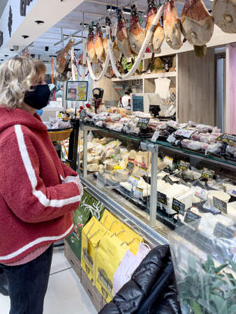 Bracciano, Rome, Italy - March, 26, 2021: Woman in front of the deli counter in a supermarket of the Gros chain buying cold cuts and cheeses for Easter lunch.