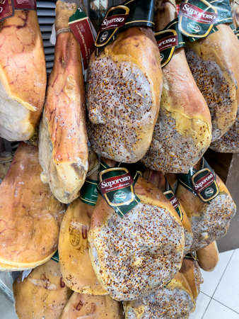 Bracciano, Rome, Italy - March 26, 2021: Cured mountain hams hanging, typical Umbrian products produced by Nursia